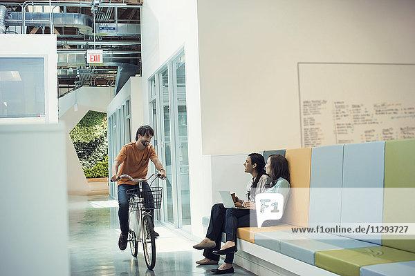 Young Professional auf dem Fahrrad trifft Kollegen in der Lobby