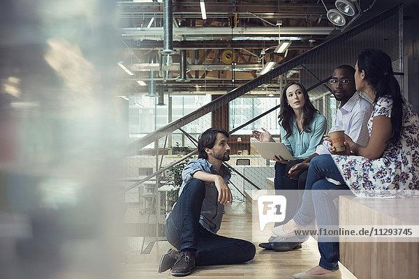 Junge Geschäftsleute diskutieren  sitzen auf der Treppe