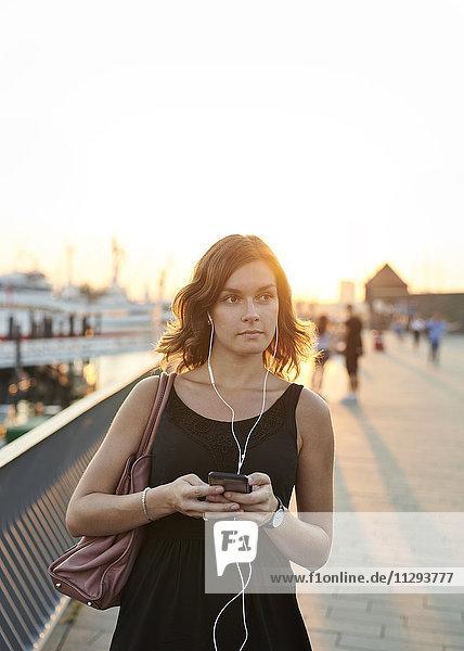 Deutschland  Junge Frau mit Smartphone erkundet Hamburg