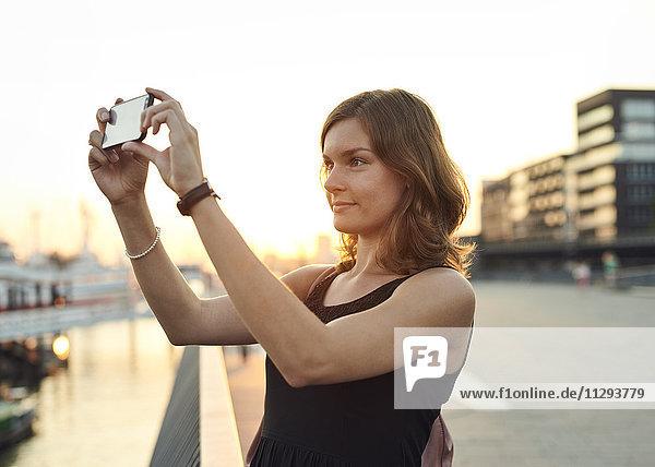 Deutschland  Junge Frau in Hamburg fotografiert mit ihrem Smartphone