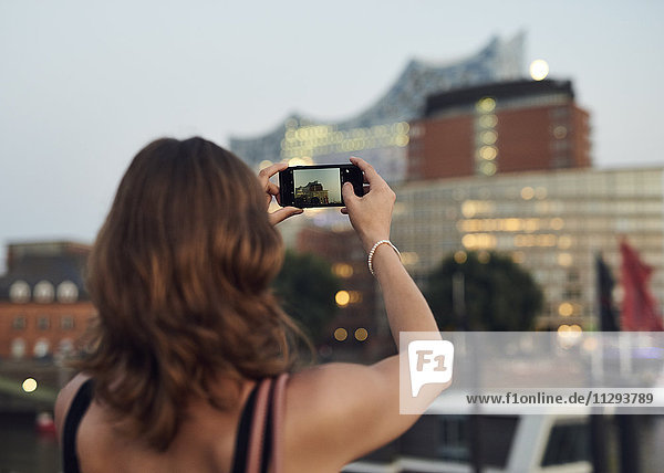 Germany  Young woman in Hamburg taking pictures with her smart phone