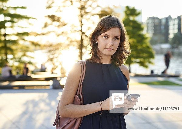 Germany  Young woman with smart phone exploring Hamburg