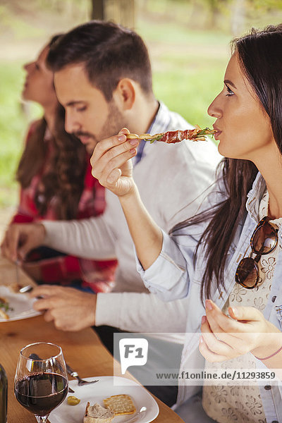 Frau mit Freunden beim Essen im Freien