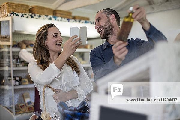 Glückliches Paar beim Fotografieren mit dem Smartphone im Hofladen