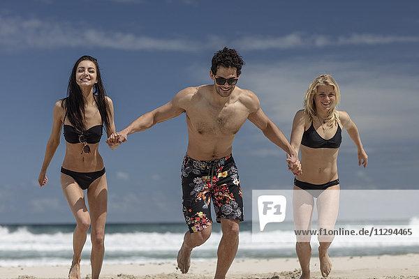 Glückliche Freunde  die am Strand laufen