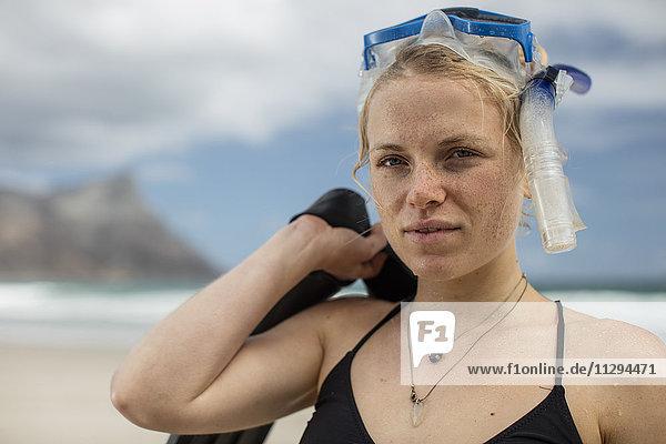Portrait einer jungen Frau mit Schnorchelausrüstung am Strand
