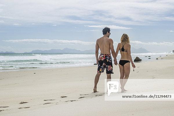 Junges Paar  das Hand in Hand am Strand geht