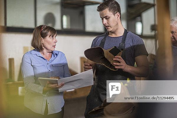 Frau mit Tablette im Gespräch mit dem Schuhmacher in der Werkstatt