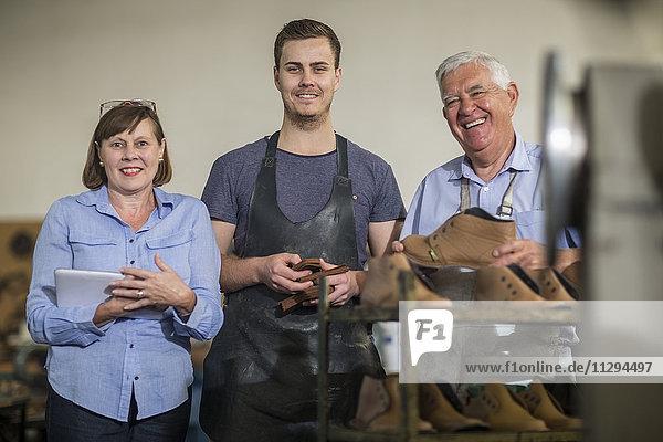 Porträt des lächelnden Personals in der Schuhmacherei