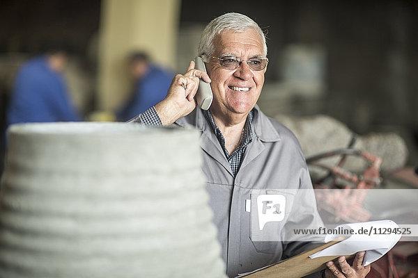 Mann mit Klemmbrett am Telefon in der industriellen Topffabrik