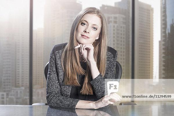 Geschäftsfrau sitzt im Büro und schaut in die Kamera.