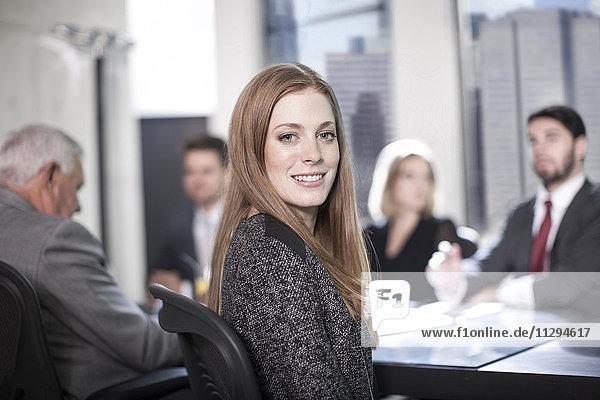 Erfolgreiche Geschäftsfrau sitzt in der Konferenz und schaut in die Kamera.