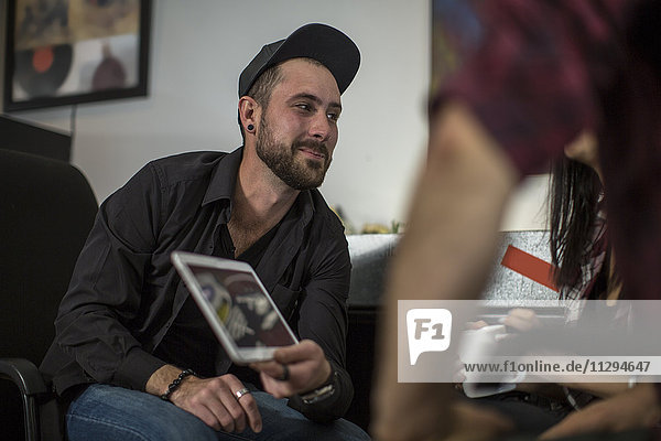 Grafikdesigner zeigt seine Arbeit auf dem Tablett in einem Meeting