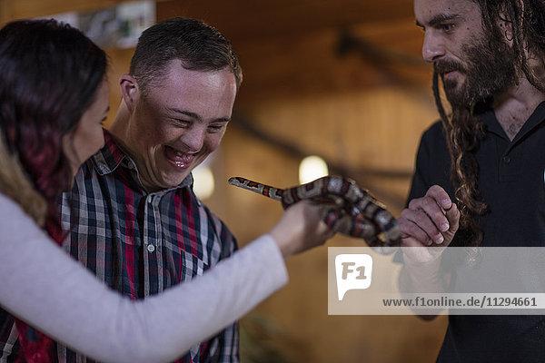 Tierpflegerin zeigt jungen Mann mit Down-Syndrom und junger Frau eine Korallenschlange.