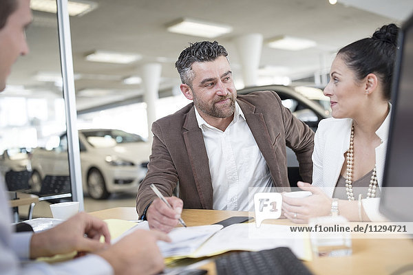 Autohaus und Pärchen am Schreibtisch mit Vertragsformularen im Showroom