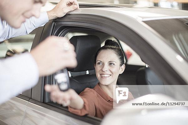 Autohändler übergibt Schlüssel an Frau im Autohaus