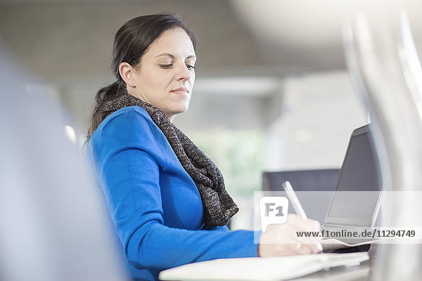 Frau am Schreibtisch mit Laptop-Schriftzug im Notebook