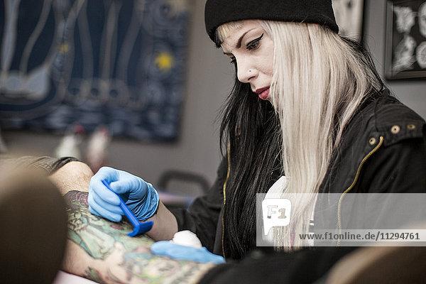 Weibliche Tätowiererin Rasierbein vor dem Tätowieren