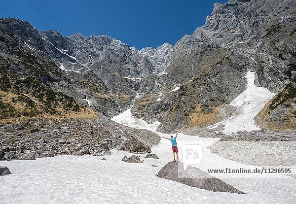 Junger Mann auf Stein  Schneefeld vor der Ostwand des Watzmann  Berchtesgadener Land  Oberbayern  Bayern  Deutschland  Europa