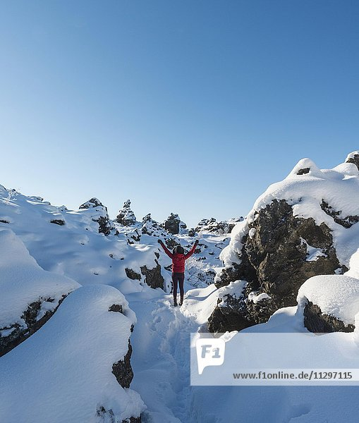 Woman with arms in the air  snowy landscape  lava field covered with snow  Krafla volcanic system  Dimmuborgir National Park  Mývatn  North Iceland  Iceland  Europe