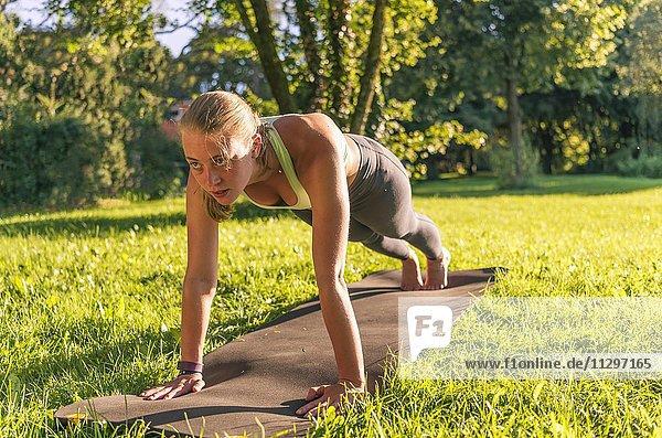 Liegestütze  Junge Frau in Sportkleidung trainiert auf einer Matte in der Wiese in einem Park  München  Oberbayern  Bayern  Deutschland  Europa