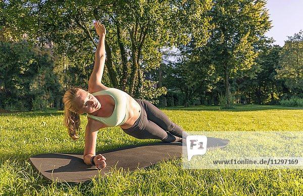 Planks auf der Seite  Junge Frau in Sportkleidung trainiert auf einer Matte in der Wiese in einem Park  München  Oberbayern  Bayern  Deutschland  Europa