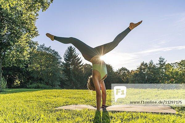 Handstand  Junge Frau in Sportkleidung trainiert auf einer Matte in der Wiese in einem Park  München  Oberbayern  Bayern  Deutschland  Europa