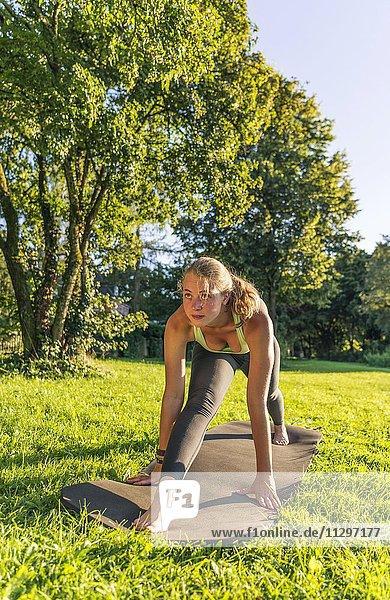 Front Splits  Spagat  Junge Frau in Sportkleidung trainiert auf einer Matte in der Wiese in einem Park  München  Oberbayern  Bayern  Deutschland  Europa