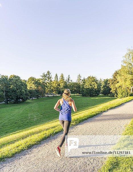 Junge Frau in Sportkleidung joggt in einem Park  München  Oberbayern  Bayern  Deutschland  Europa