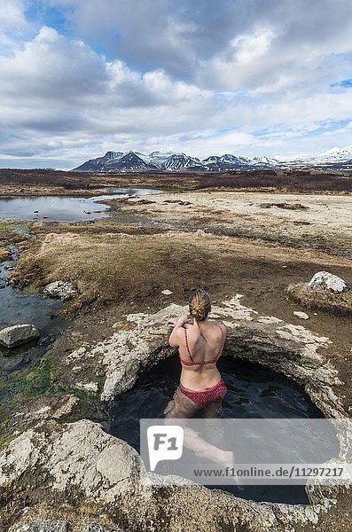 Junge Frau in einer heißen Quelle blickt auf Berge  bei Eyjar og Miklaholt  Vesturland  Island  Europa