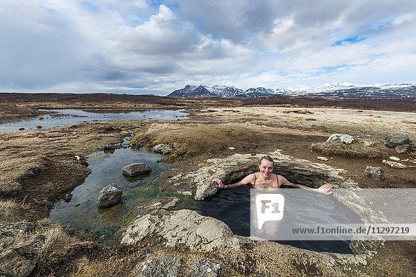 Young woman in hot spring  Eyjar og Miklaholt  Western Region  Iceland  Europe