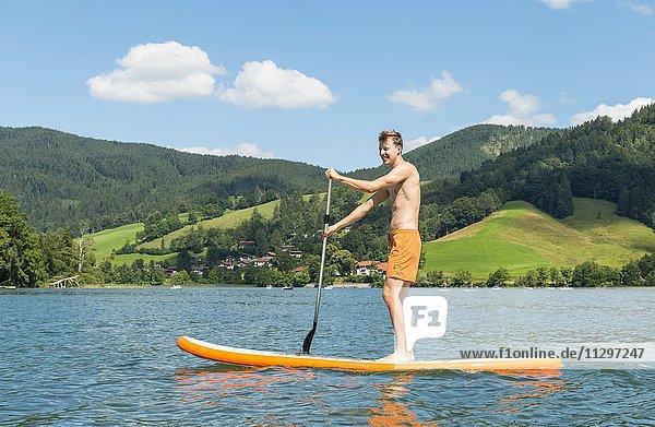 Junger Mann auf einem Stehpaddel  Stand-Up-Paddel oder SUP auf einem See  Schliersee  Oberbayern  Bayern  Deutschland  Europa