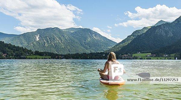 Junge Frau sitzt auf einem Stehpaddel  Stand-Up-Paddel oder SUP  hinten Berge  Schliersee  Oberbayern  Bayern  Deutschland  Europa