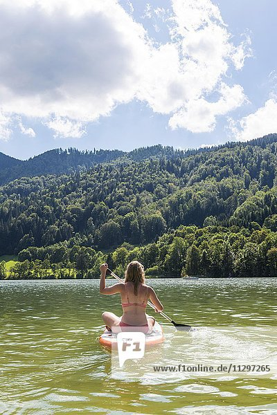 Junge Frau sitzt auf einem Stehpaddel  Stand-Up-Paddel oder SUP  Schliersee  Oberbayern  Bayern  Deutschland  Europa