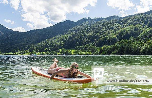 Junge Frau liegt auf einem Stehpaddel  Stand-Up-Paddel oder SUP und paddelt mit den Händen im See  Schliersee  Oberbayern  Bayern  Deutschland  Europa