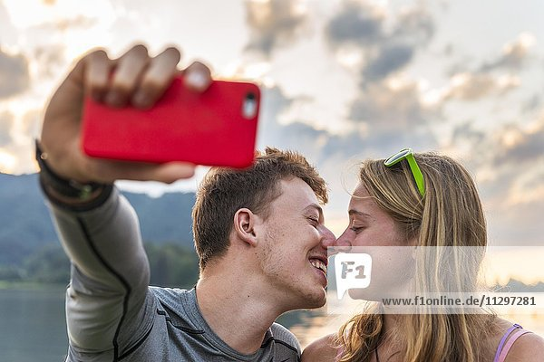 Junges Paar küsst sich  fotografiert sich mit einem Handy selbst  Selfie  Schliersee  Oberbayern  Bayern  Deutschland  Europa