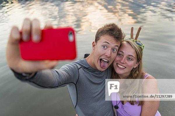 Junges Paar fotografiert sich mit einem Handy selbst  Selfie  Schliersee  Oberbayern  Bayern  Deutschland  Europa