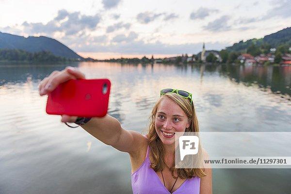 Junge Frau lächelt  fotografiert sich mit einem Handy  Selfie  Schliersee  Oberbayern  Bayern  Deutschland  Europa