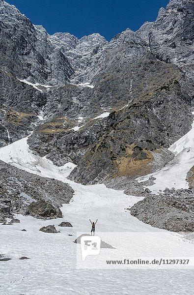Wanderin steht auf Stein mit ausgestreckten Armen  tiefstes Schneefeld der Deutschen Alpen  Watzmann Ostwand  Berchtesgaden  Bayern  Deutschland  Europa