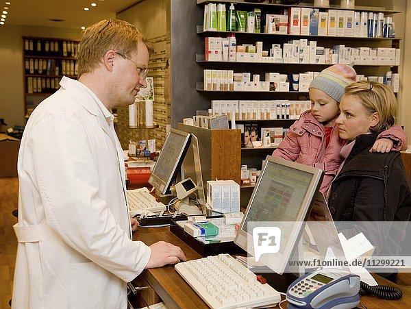 Apotheker und Mutter mit Tochter im Verkaufsgespräch  Beratung in der Apotheke  Deutschland  Europa