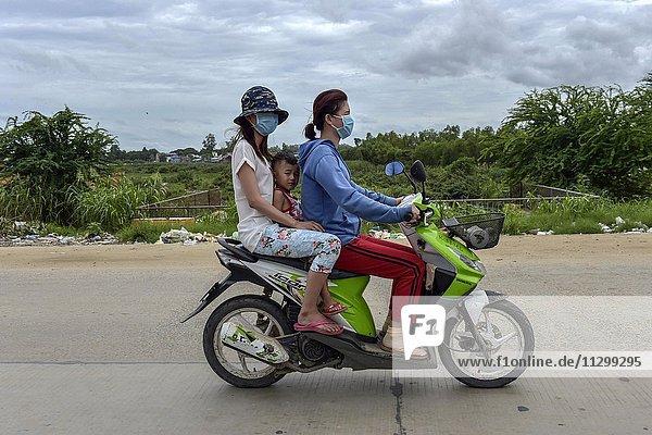 Zwei Frauen mit Kind auf einem Motorroller  Phnom Penh  Kambodscha  Asien