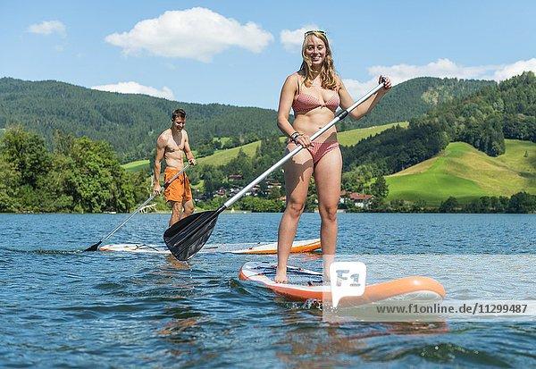 Junger Mann und junge Frau auf einem Stehpaddel Board  Stand-Up-Paddel oder SUP auf einem See  Schliersee  Oberbayern  Bayern  Deutschland  Europa