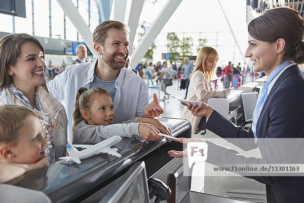 Kundendienstmitarbeiter hilft der Familie beim Einchecken mit Tickets am Check-in-Schalter des Flughafens.