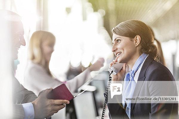 Kundenbetreuer im Telefongespräch mit dem Geschäftsmann am Flughafen-Check-in-Schalter