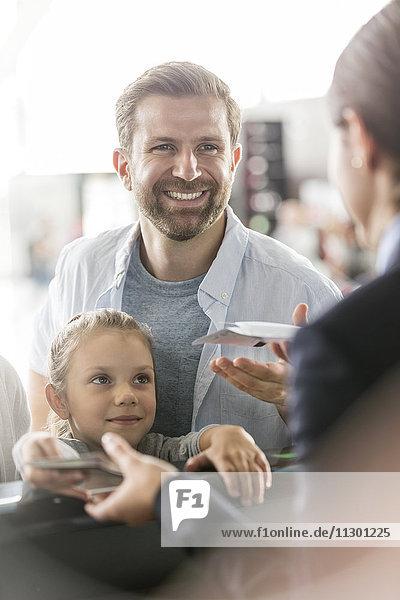 Vater und Tochter mit Flugtickets am Flughafen-Check-in-Schalter