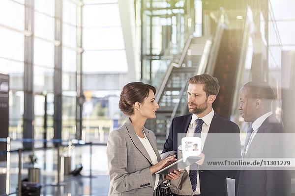Geschäftsleute mit digitalem Tablett sprechen am Flughafen