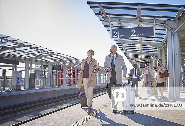 Geschäftsleute ziehen Koffer auf dem sonnigen Bahnsteig des Bahnhofs