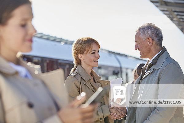 Geschäftsmann und Geschäftsfrau beim Händeschütteln auf dem sonnigen Bahnsteig des Bahnhofs