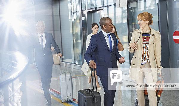Geschäftsleute beim Reden und Gehen mit Koffern in der Flughafenhalle