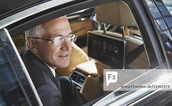 Geschäftsmann schaut aus dem Stadtautofenster